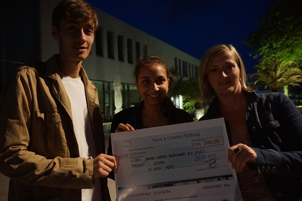Tim Pathe und Melanie Lal aus dem Vorstand des junge medien thüringen e.V. bekommen am Studiopark Kindermedienzentrum von Frau Warmuth den 500-Euro-Scheck der Town&Country-Stiftung.